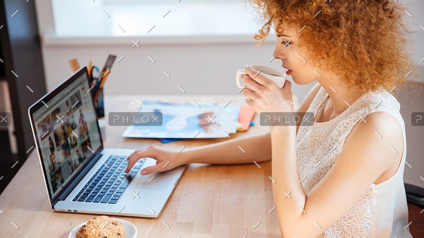 demo-attachment-177-woman-photographer-drinking-coffee-and-working-PJNBP6U